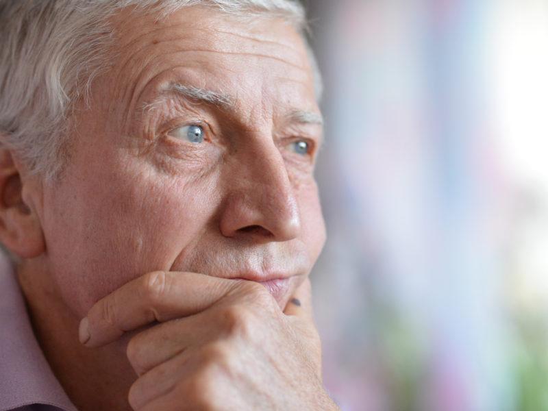 Elderly male, sad.